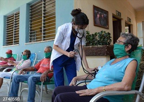 Personal sanitario atendiendo a una persona con mascarilla en Cuba