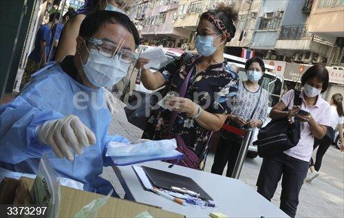 Personal médico de un centro hospitalario de Hong Kong atiende a un grupo de personas que se van a someter a la prueba de coronavirus.<br>Fecha: 14/10/2020.
