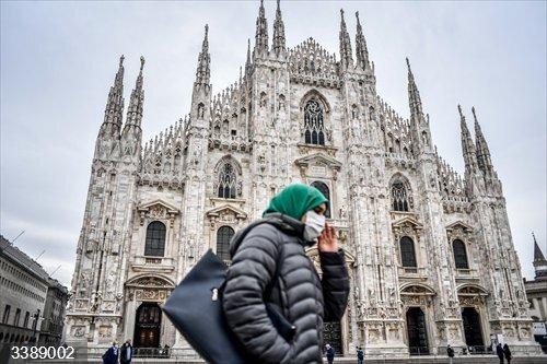 22 October 2020, Italy, Milan: A woman walks past the Milan Cathedral wearing a face mask. Photo: Claudio Furlan/LaPresse via ZUMA Press/dpa
