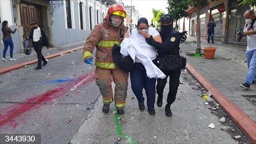 Una mujer afectada por el gas lacrimógeno y un policía durante las protestas contra el presidente Alejandro Giammattei en Guatemala<br>REMITIDA / HANDOUT por POLICÍA DE GUATEMALA<br>Fecha: 22/11/2020.                 <br>Fotografía remitida a medios de comunicación exclusivamente para ilustrar la noticia a la que hace referencia la imagen, y citando la procedencia de la imagen en la firma